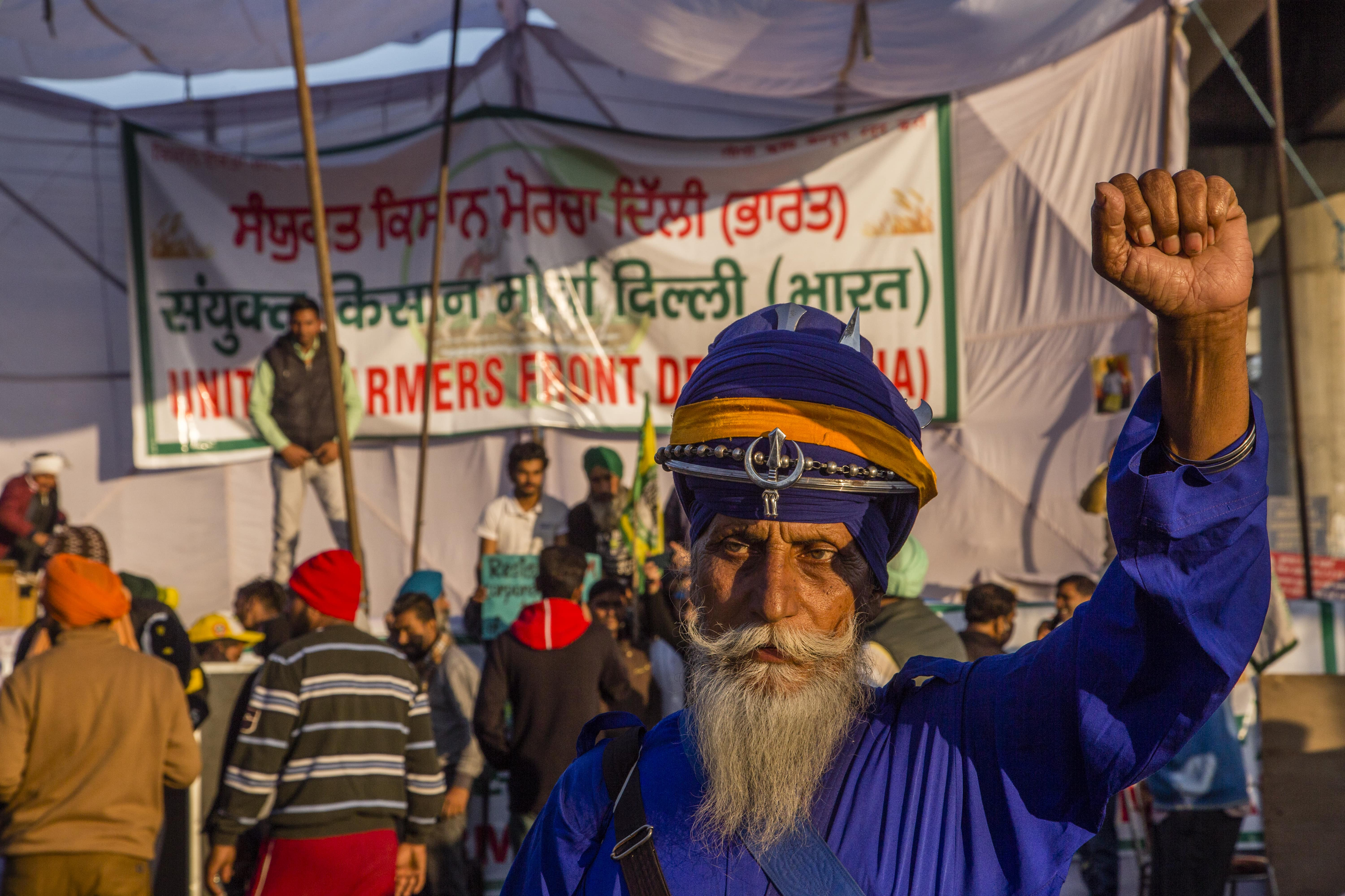 A bearded man dressed all in blue raises up his fist at a political rally for Indian farmers.