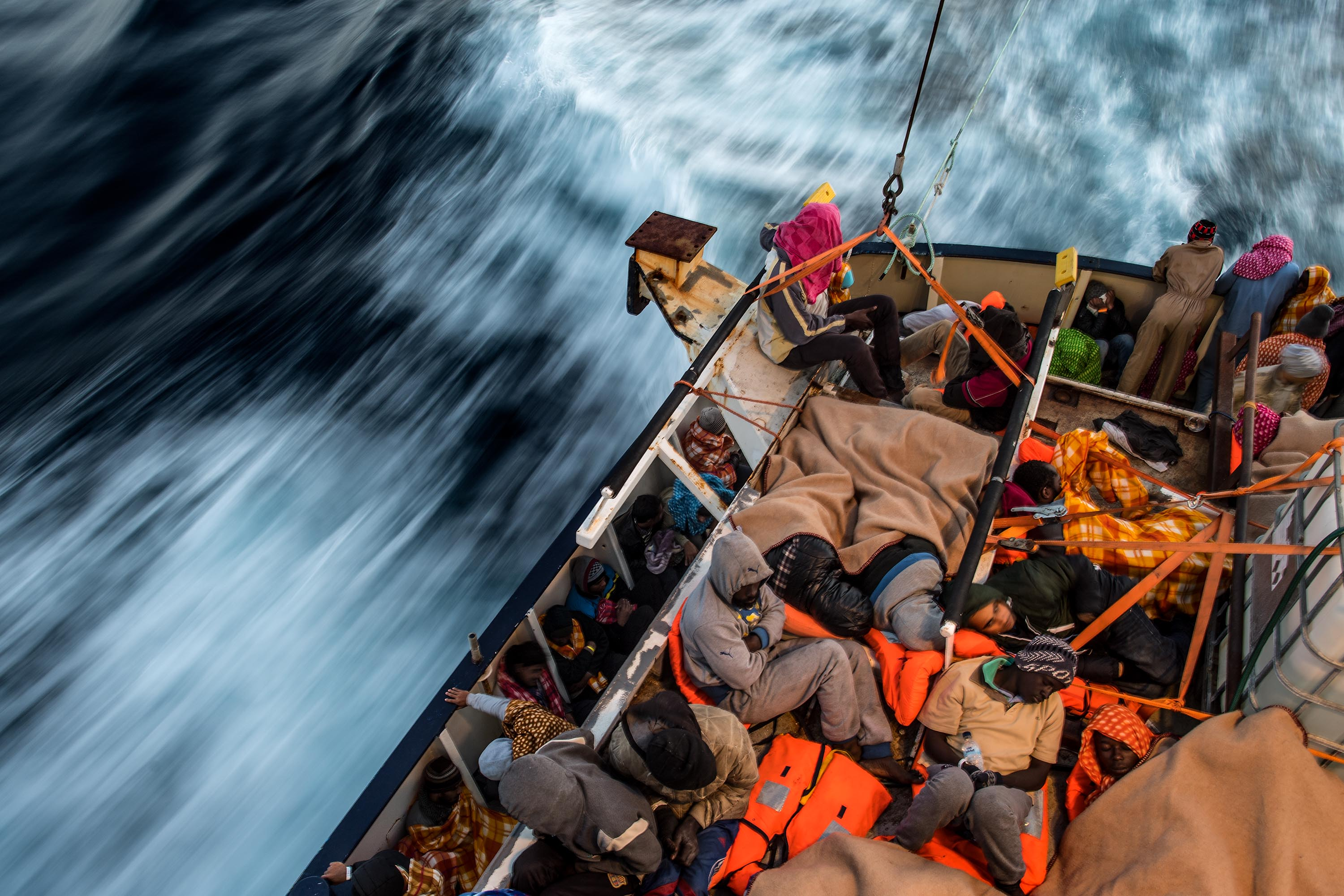 A picture of migrants packed together tightly in a boat sailing on the sea.