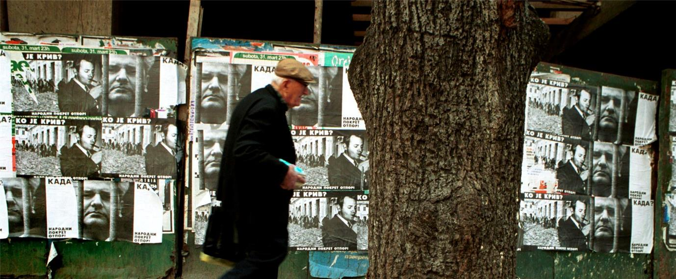 An image of an old man walking past a wall plastered over with news pamphlets.