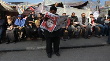 "Protesters at an encampment in Tahrir Square begin the day reading newspapers detailng the resignation of President Hosni Mubarak, the headline reads ""Finally he is out"", on February 12, 2011 in Cairo, Egypt."