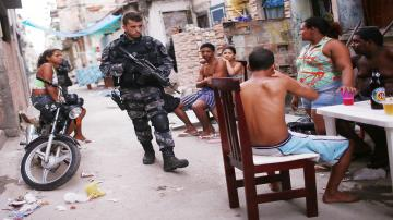 A Brazilian military police officer patrols after entering the unpacified Complexo da Mare, one of the largest 'favela' complexes in Rio, on March 30, 2014 in Rio de Janeiro, Brazil.
