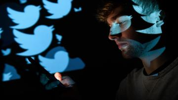 A picture of a man scrolling on his phone in a dark room while the Blue Twitter logo is projected on the wall behind him.